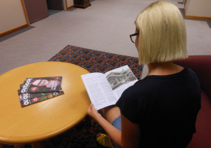 A woman sitting at a coffee table reading Outlook magazine