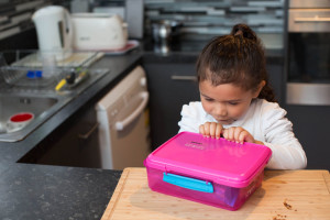 a little girl with her lunchbox on the kitchen bench