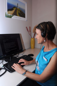Woman sitting at her work computer with headphones