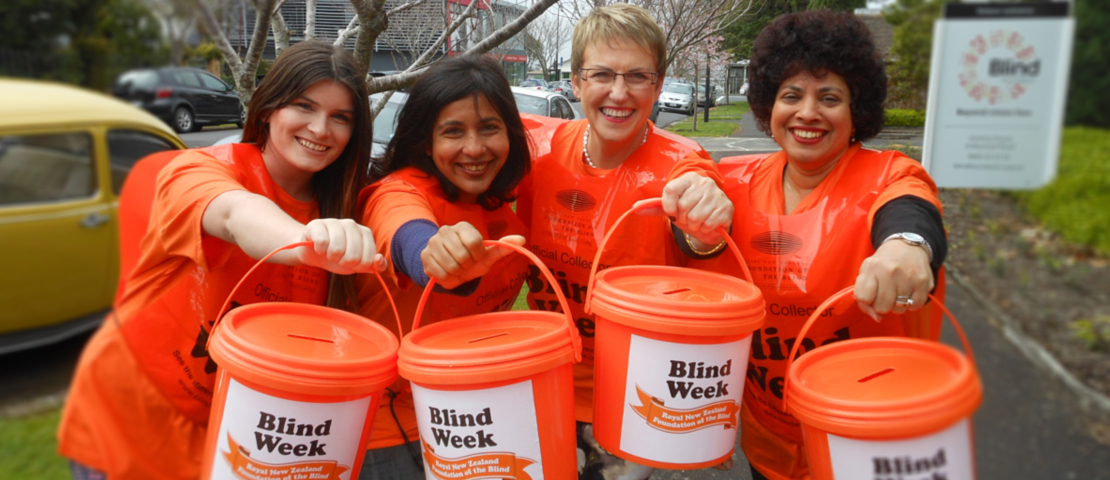 A group of Blind Week street collectors holding out orange buckets