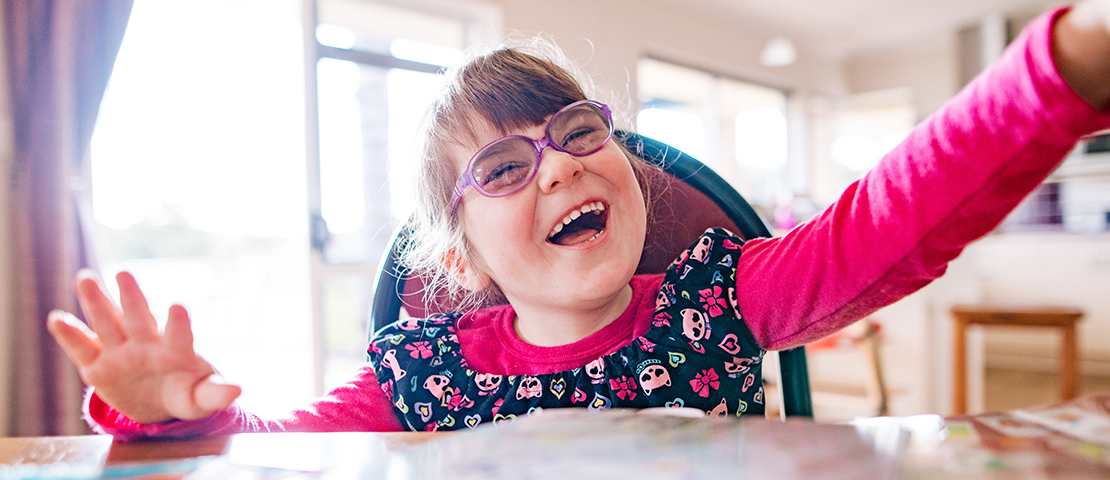 A young girl in purple glasses laughing