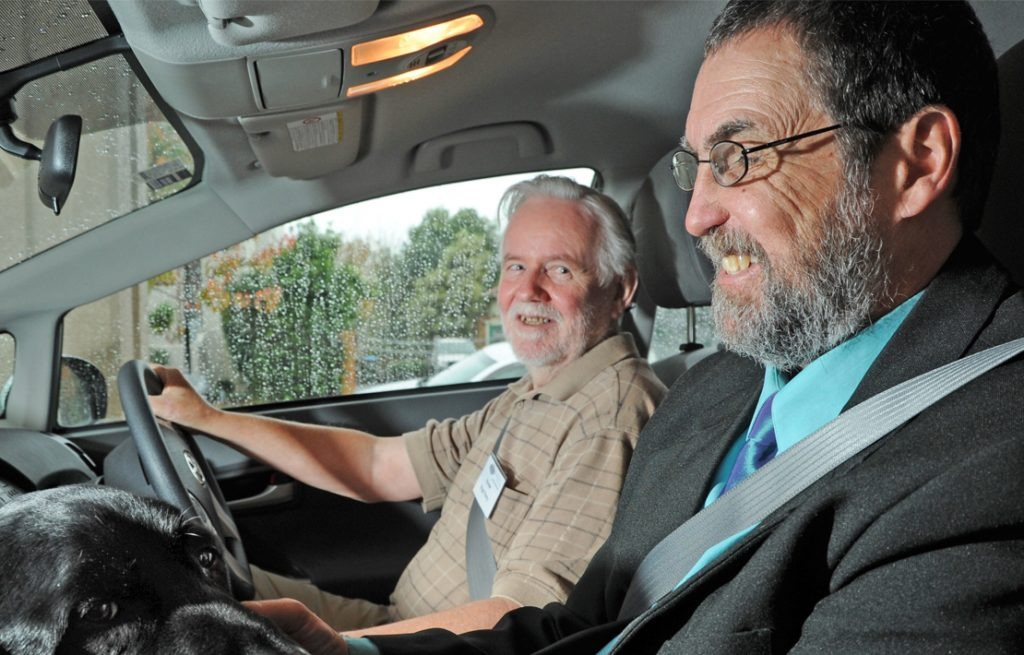 A volunteer driver driving a man and his guide dog