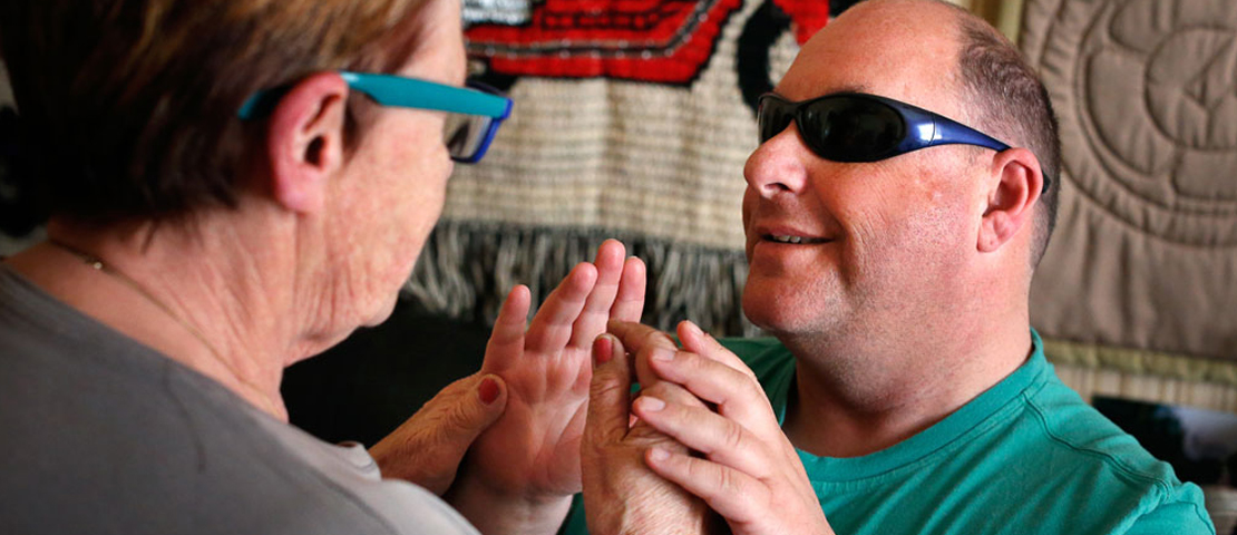 A deaf blindman using tactile sign language to talk to a woman
