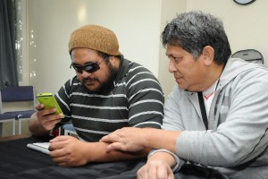 Two Pacific Island clients looking at an iphone and ipad