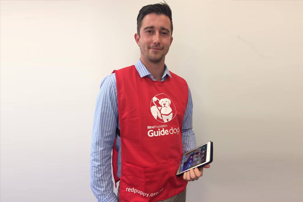 Door to door fundraiser in red guide dogs bib