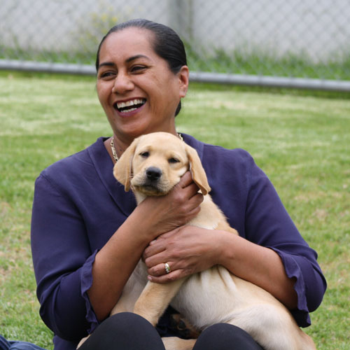 smiling lady with a guide dog puppy in her lap