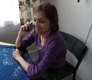 Woman sitting at a table on the phone using TIS