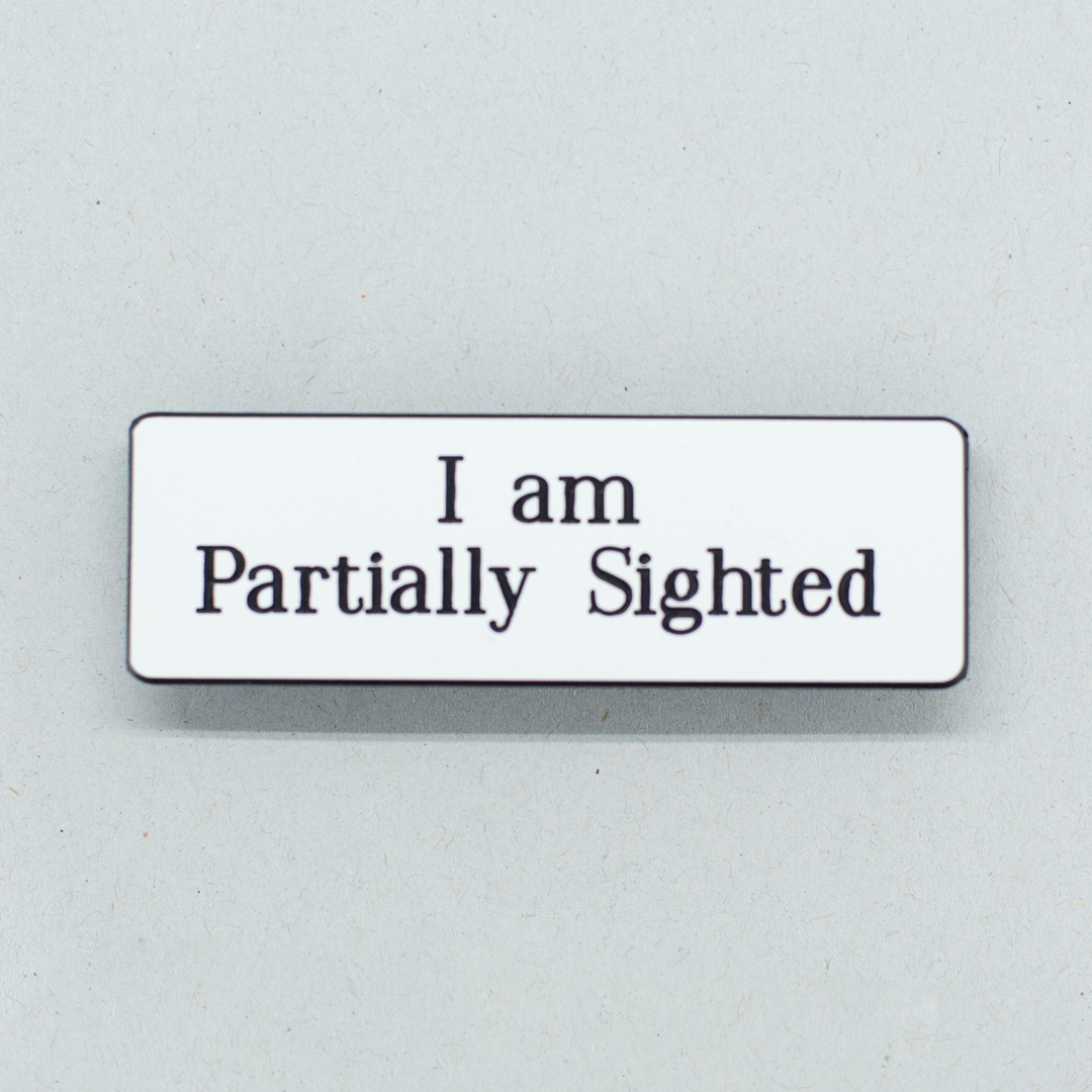 White lapel badge with black text that says I am Partially Sighted