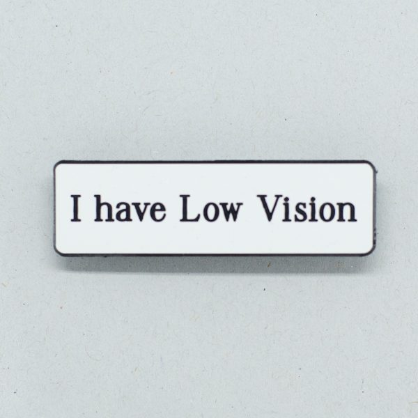 White lapel badge with black text that says I have Low Vision