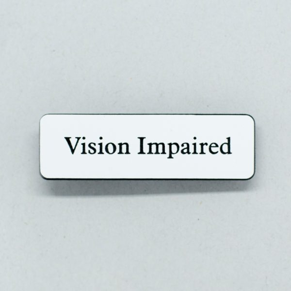 Small white badge with black text that says Vision Impaired