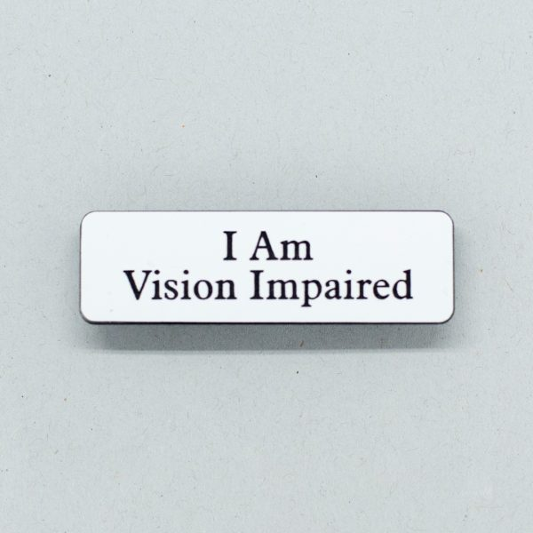 Small white badge with black text that says I Am Vision Impaired