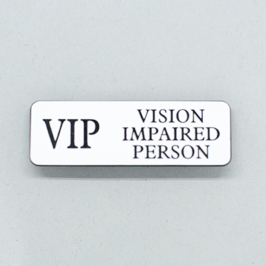White lapel badge with black text that says VIP Vision Impaired Person