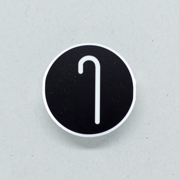 Small round badge with a white cane symbol
