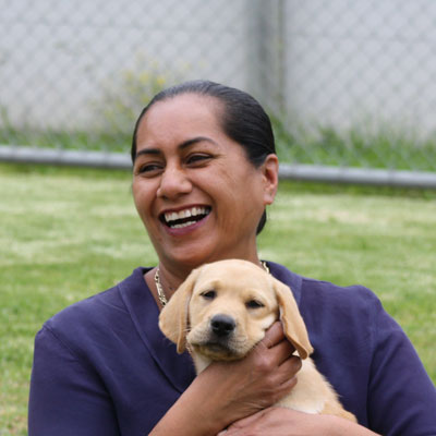 lady smiling holding a yellow guide dog puppy