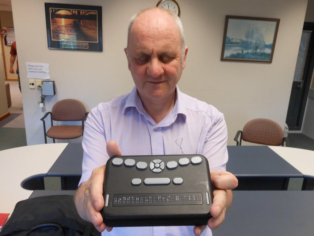 Neil Jarvis holding the orbit braille reader