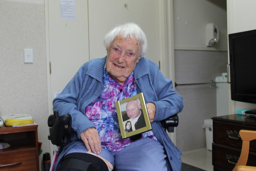 Helen Beeb holding a photo of her familty