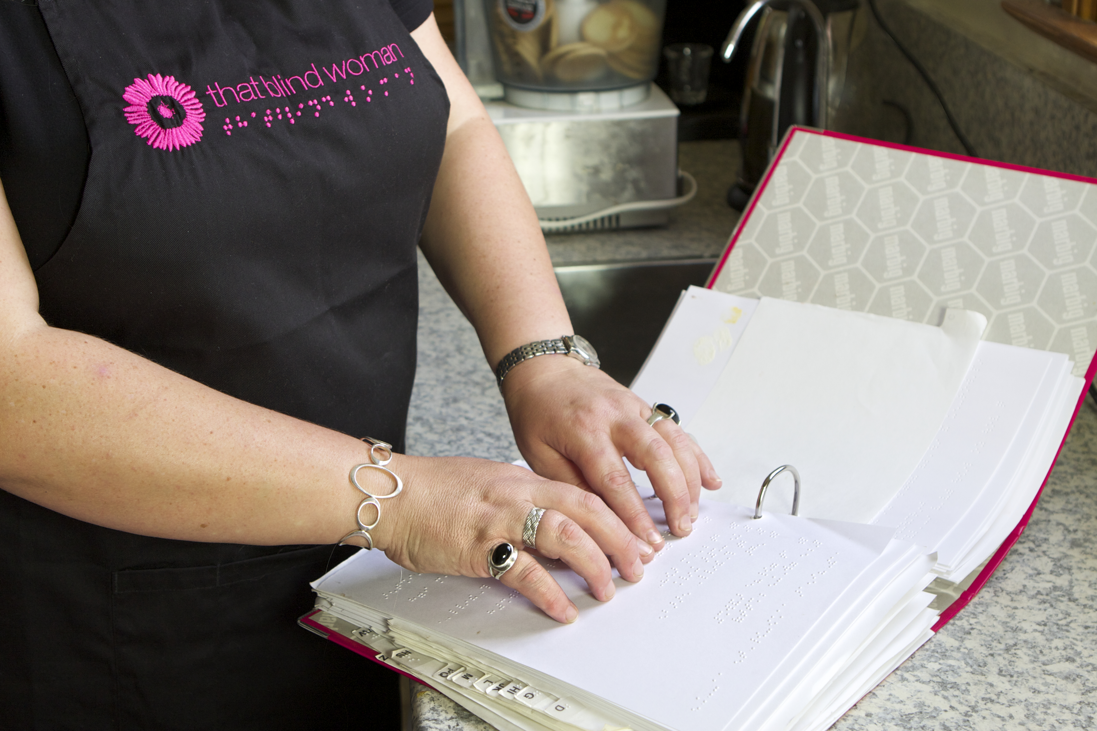 Photo of Julie Woods reading a braille recipe