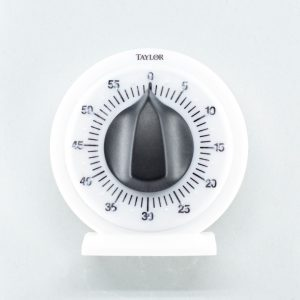 A white kitchen timer with a black dial