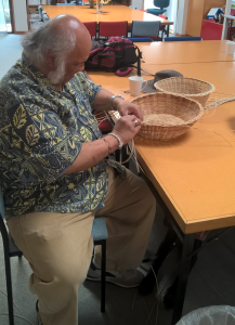 Craft group member weaving a basket