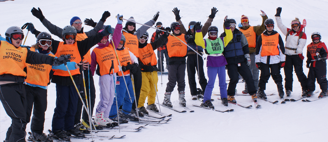 A group of skiers wearing orange vests that saying visually impaired
