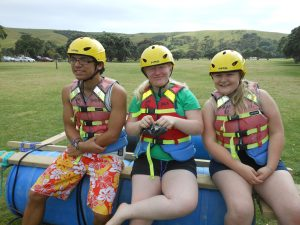 Three young people wearing helmets prepare to go rafting