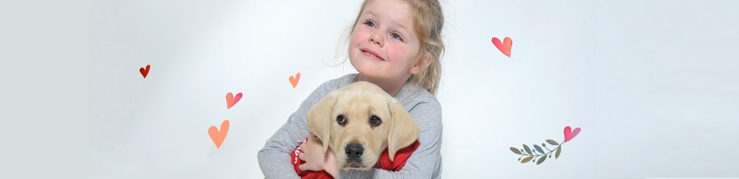 5 year old Asha hugging a guide dog puppy