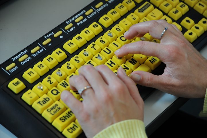 Image shows hands typing on a braille keyboard