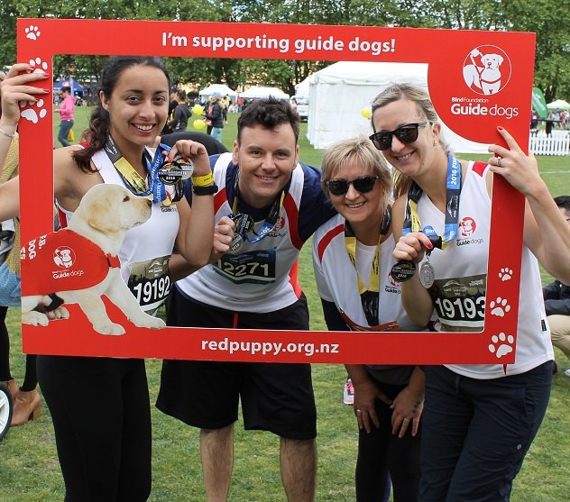 Last year's Team Guide Dogs marathon participants holding a Team Guide Dogs frame