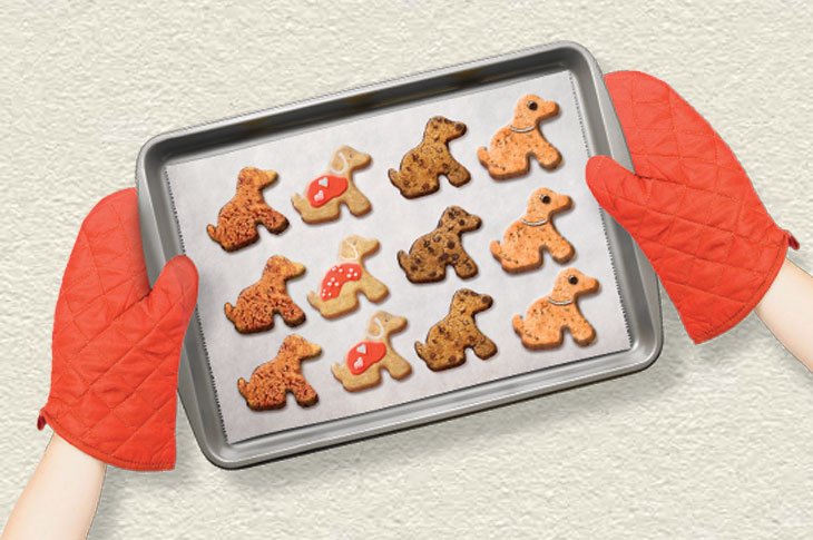 Hands holding a tray of puppy shaped biscuits