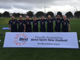 Image shows the New Zealand Blind Rugby squad posing with a Blind Foundation banner.