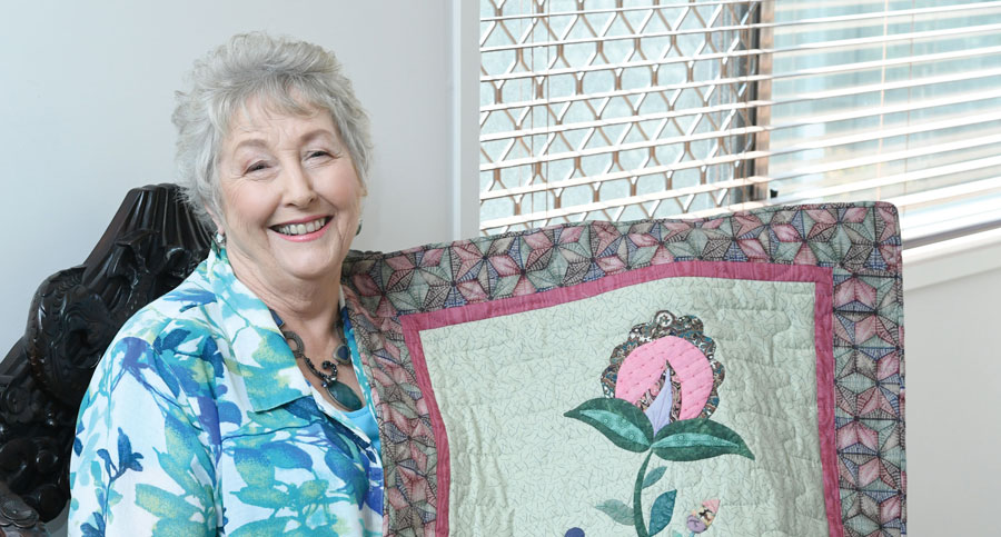 An old lady smiling and holding up her quilt