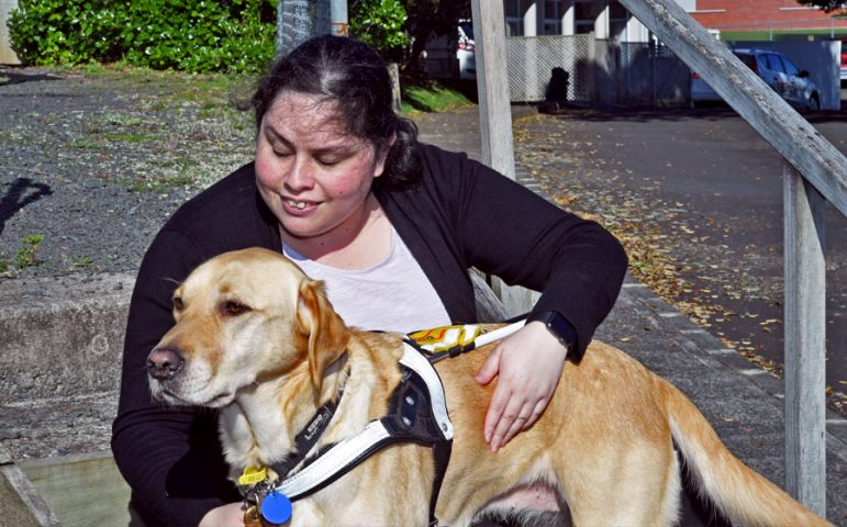 Chantelle sitting on the steps with guide dog Darbi