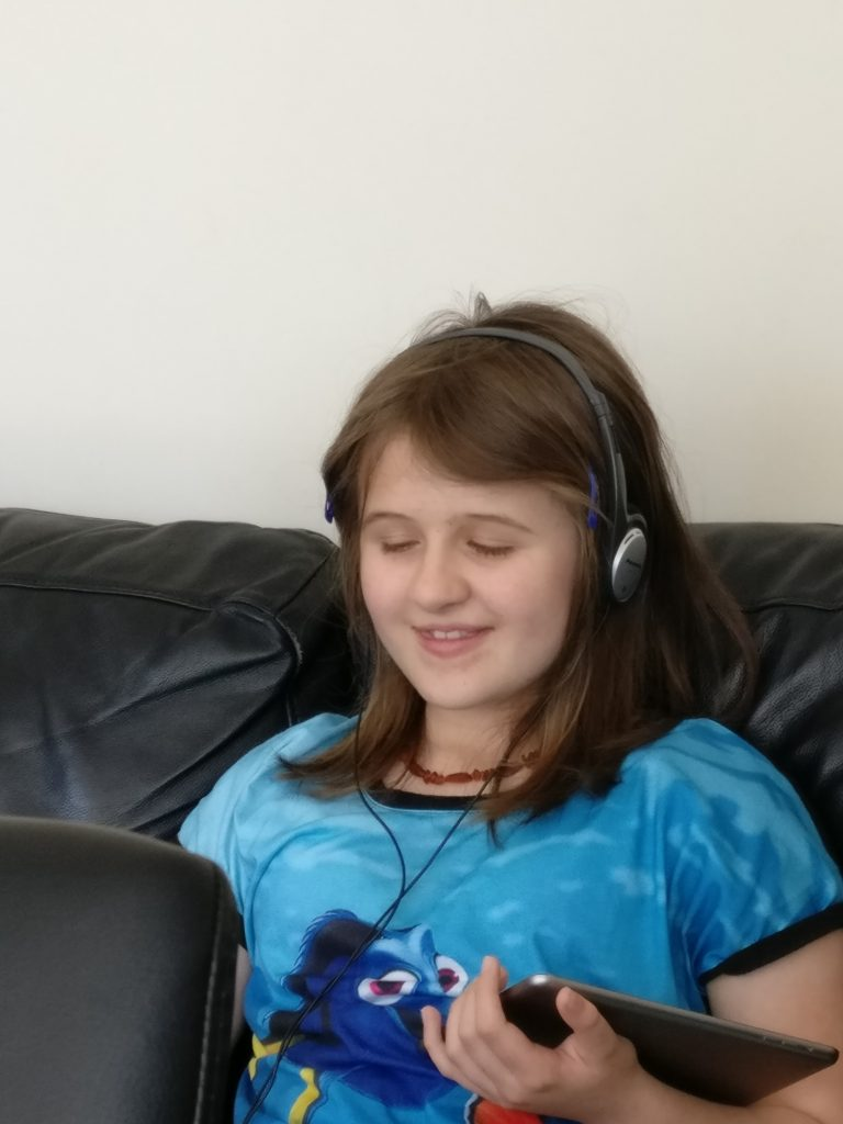 Brianna Houston listening to something on her tablet using headphones