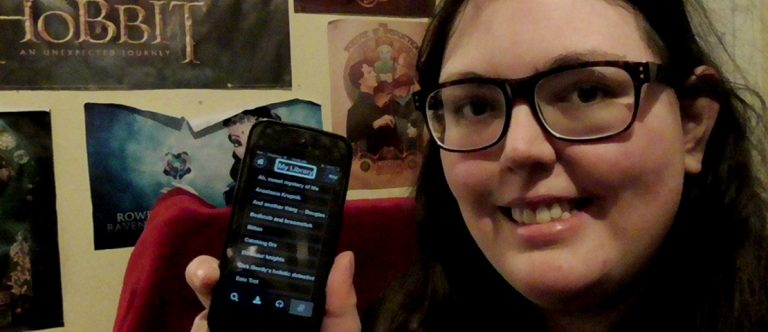 A young woman holding up her iPhone with the BookLink app open