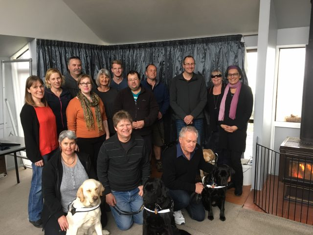 Image shows the Peer Mentoring group and their guide dogs posing in front of a curtain.