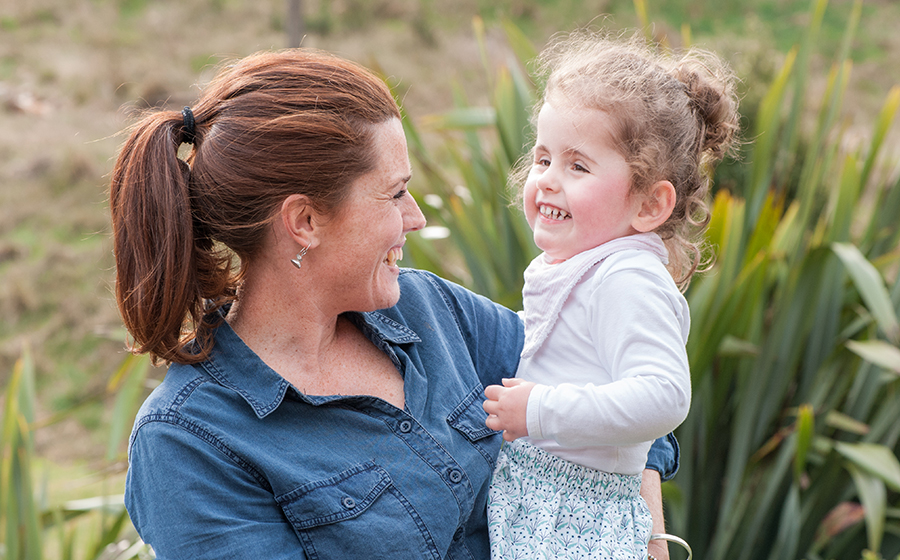 Mum Hayley smiling and holding her daughter Lottie