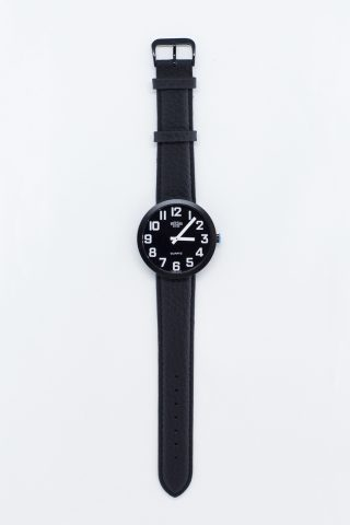 Image shows low vision watch with black face and white numbers.
