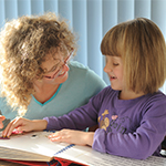 A young girl reading a braille book with her mum