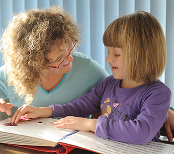 A young girl reading a tactile book with her mum