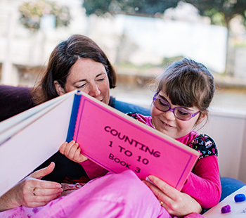 Laura and mum reading a tactile book together