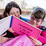 A mum and daughter reading a large print book