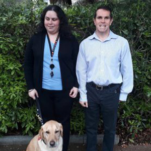 Chantelle Griffiths, Mike Lloyd and guide dog Darbi stand in front of a leafy background.