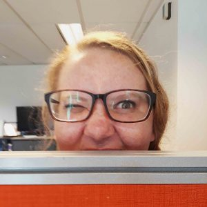 Rachel Shardlow peeks up from behind an office room divider.