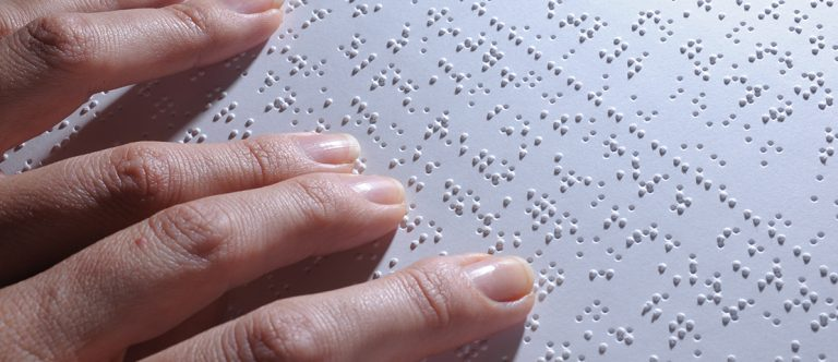 Close up of hands reading braille