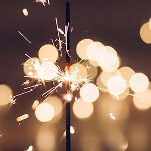 Lit sparkler against a dark background.