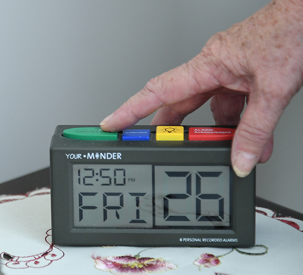 Hands turning off a talking clock alarm