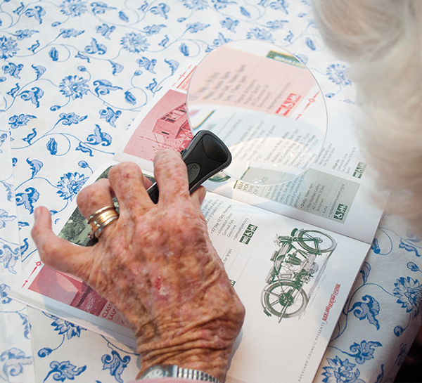 An older woman using a hand held magnifier to read a magazine