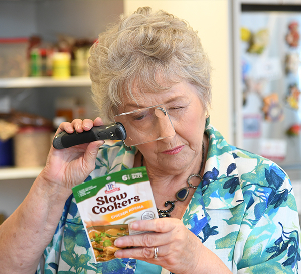 An older woman using a hand held magnifier to read the label of packet