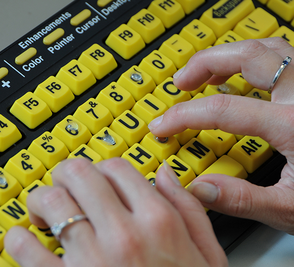 Hands typing on a bright yellow keyword with tactile dots