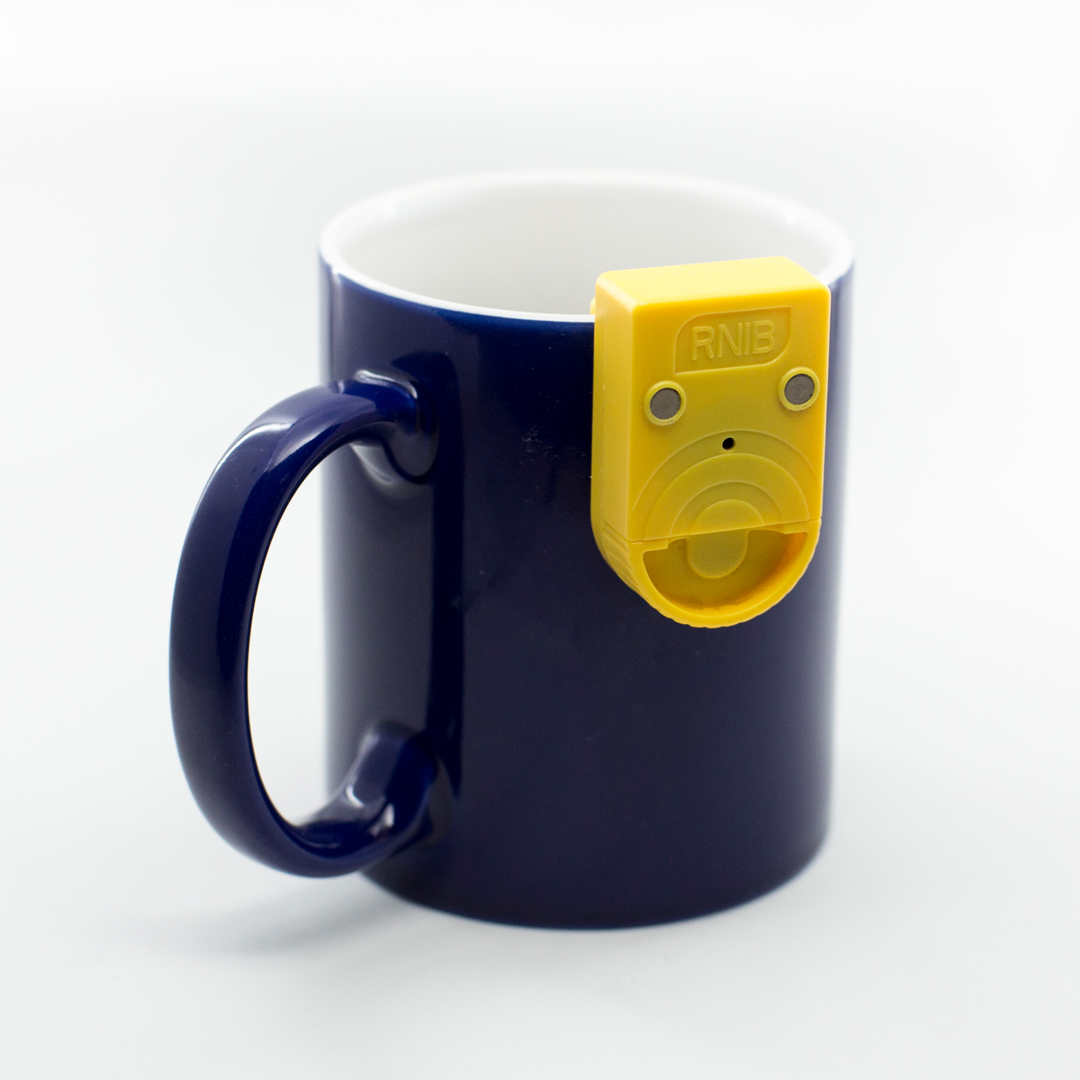 A mug with a yellow audible vibratory liquid level indicator attached